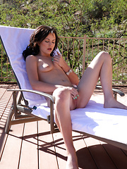 Gorgeous brunette spreads her sweet pink twat while sunbathing